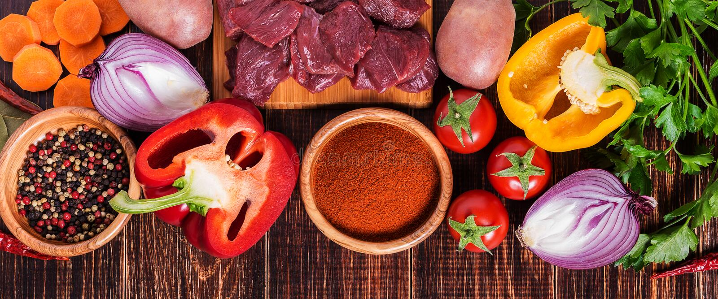 Ingrédients pour la cuisson de goulache : viande crue, herbes, épices, légumes photo stock
