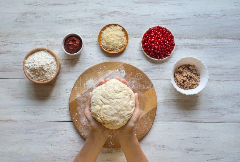 Ingrédients pour la pizza sur la table : pâte crue, thon haché, parmesan râpé et graines de grenade photos stock