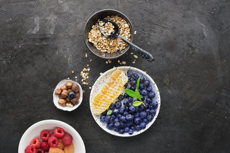 Ingrédients pour les repas sains de petit déjeuner : framboises, myrtilles, écrous, orange, bananes, raisins bleu, vert, pommes photos stock