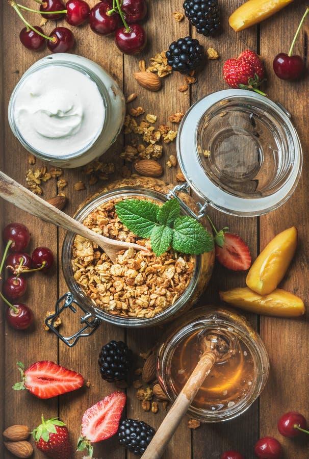 Ingrédients sains de petit déjeuner La granola d'avoine en pot, yaourt et miel ouverts a servi avec des baies, écrous, feuilles e image stock