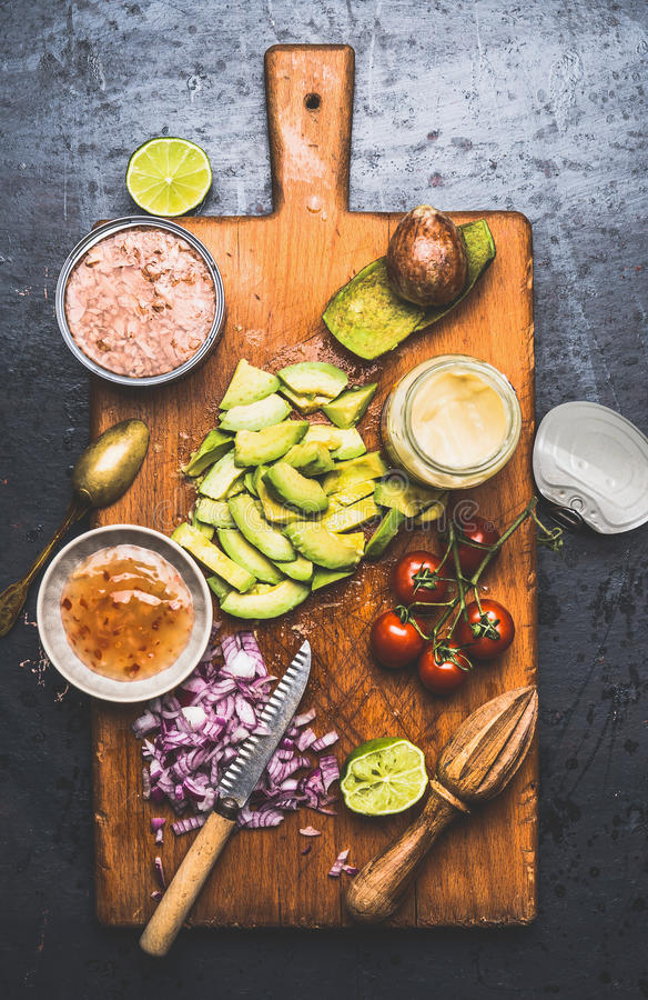Ingrédients sains de salade de thons : conserve de thon, avocat coupé, tomates et chaux sur la planche à découper rustique et le  images stock