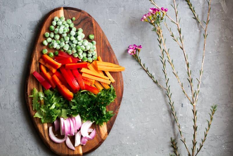 Ingrédients végétariens organiques pour une salade avec de la laitue, le poivron doux et les pois surgelés sur la planche à décou photo stock