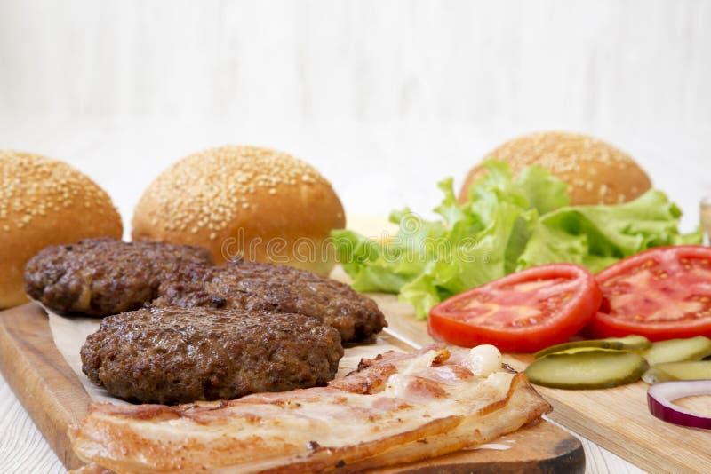 Ingr?dients d'hamburger sur une surface en bois blanche, vue de c?t? Plan rapproch? image libre de droits