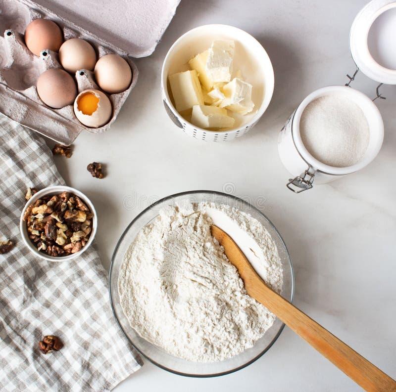 Ingr?dients pour le g?teau de cuisson Oeufs, farine, sucre et batteur, écrous de beurre Vue sup?rieure flatlay photographie stock