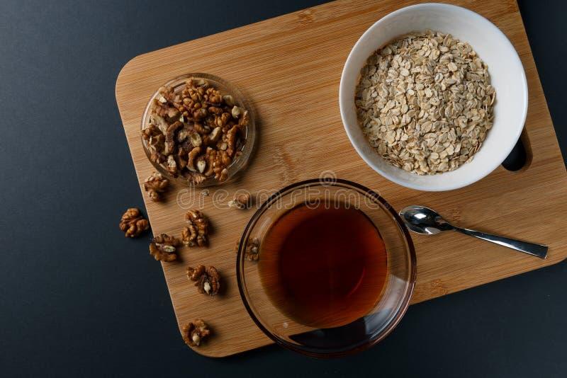 Ingr?dients sains de petit d?jeuner : miel, noix, farine d'avoine sur un fond fonc? photos libres de droits