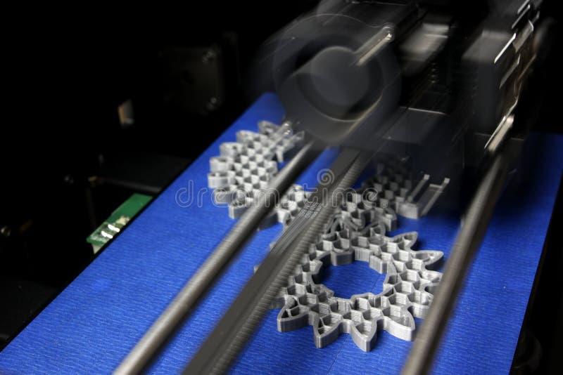Ingranaggi cilindrici di fabbricazione di FDM 3D-printer dal filamento argento-grigio su nastro della stampa blu fotografia stock libera da diritti