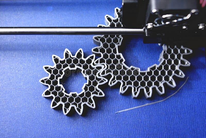 Ingranaggi cilindrici di fabbricazione di FDM 3D-printer dal filamento argento-grigio su nastro della stampa blu - vista superior fotografia stock libera da diritti