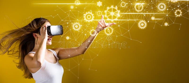 Ingranaggi con la donna che per mezzo di una cuffia avricolare di realtà virtuale fotografie stock