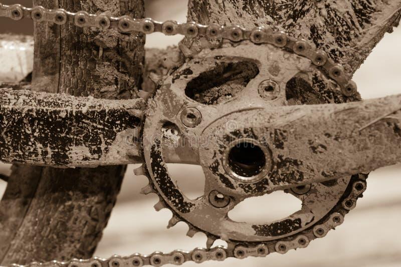 Ingranaggi della bici con la catena (fuoco selettivo) Fine sudicia su di bicyc immagine stock libera da diritti
