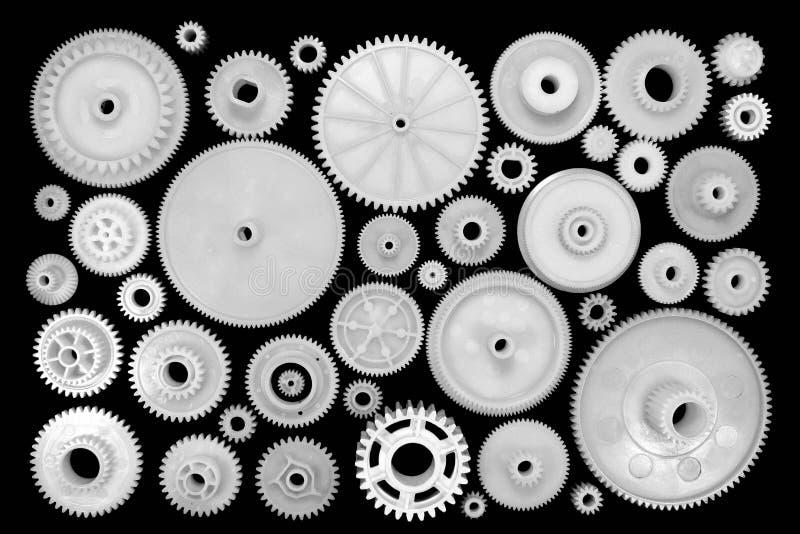 Ingranaggi e ruote dentate di plastica bianchi su fondo nero fotografia stock libera da diritti