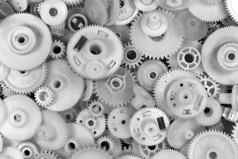 Ingranaggi e ruote dentate di plastica bianchi su fondo nero immagini stock libere da diritti