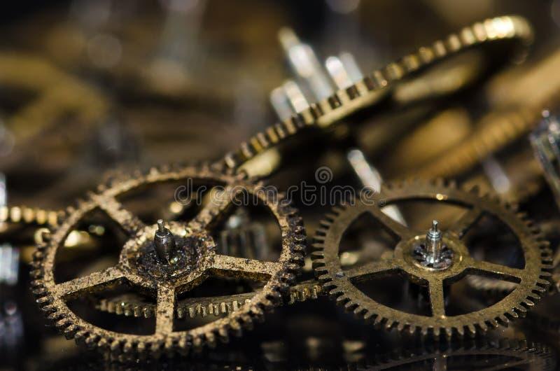 Ingranaggi metallici d'annata sporchi e sudici dell'orologio su una superficie nera fotografie stock libere da diritti