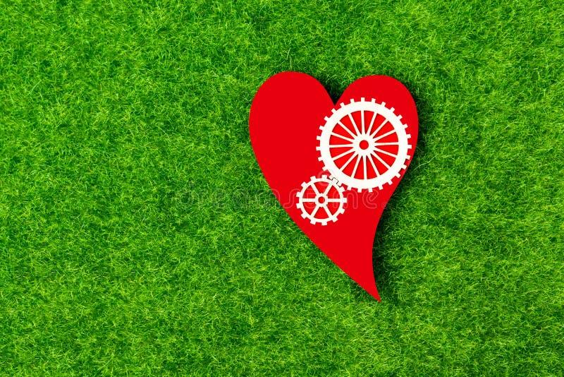 Ingranaggi, un cuore di colore rosso contro lo sfondo di erba verde artificiale fotografia stock
