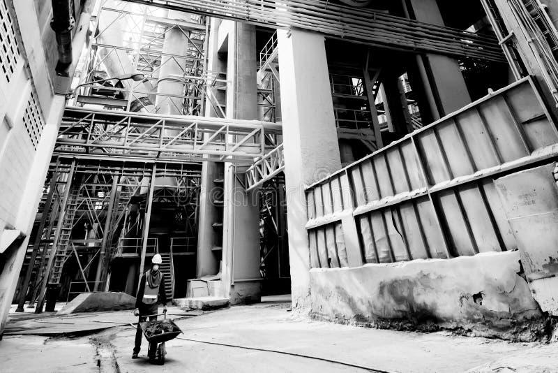Ingranaggio protettivo d'uso di sicurezza del lavoratore asiatico maschio con acque luride dentro una carriola alla fabbrica del  fotografie stock