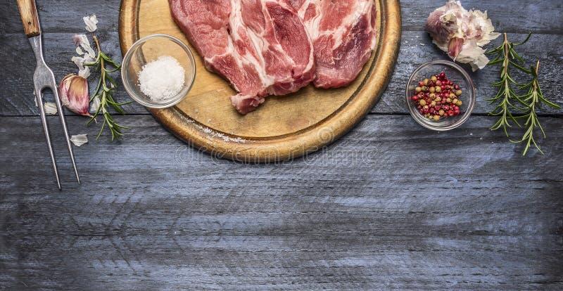 Ingrediënten en kruiden voor het braadstukvarkensvlees op een raad met een vork, op een houten achtergrond, Grens stock fotografie