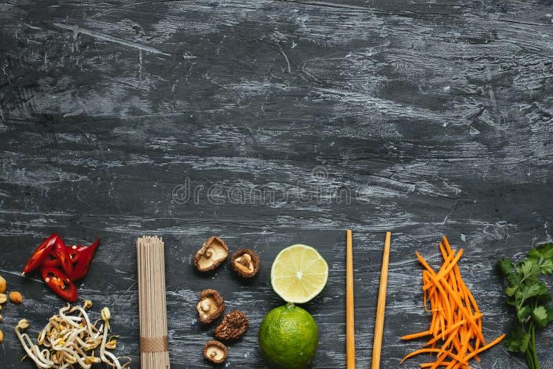 Ingrediënten voor Aziatische schotel Droge Aziatische sobanoedels met verschillende ingrediënten op houten achtergrond met exempl stock foto's