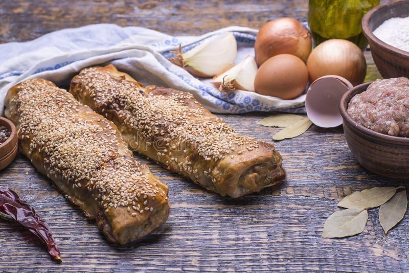Ingrediënten voor baksel - eieren, olijfoli, deeg, krachtvlees en vers gebakken eigengemaakte vleespastei op een houten lijst royalty-vrije stock afbeelding