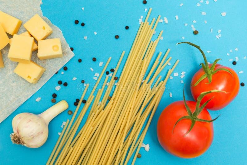 Ingrediënten voor de voorbereiding van deegwaren Spaghetti, kaas, tomaten, knoflook, op een blauwe achtergrond royalty-vrije stock foto's