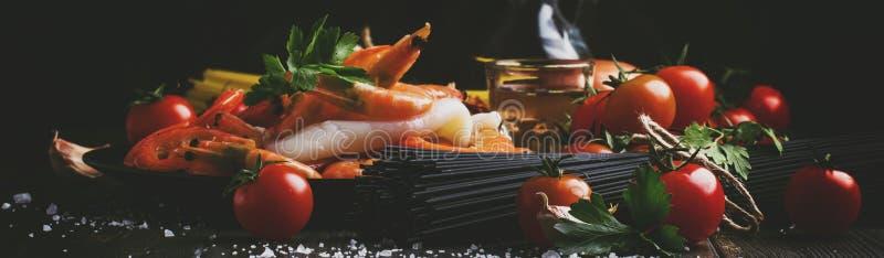 Ingrediënten voor de voorbereidings zwarte deegwaren met zeevruchten, tomaten en witte droge wijn, zwarte voedsel kokende achterg stock afbeeldingen