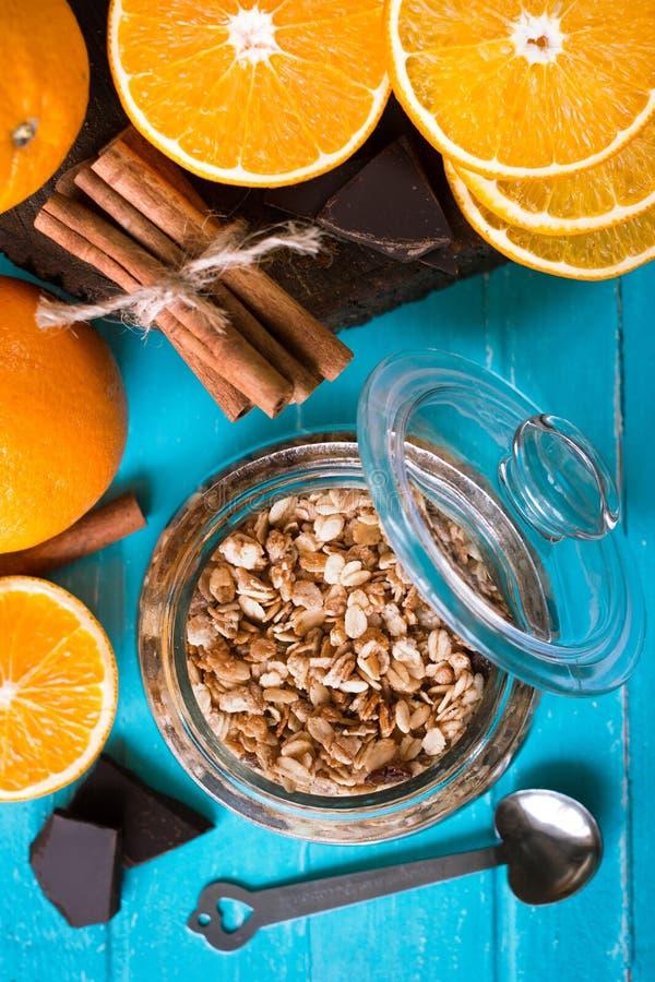 Ingrediënten voor een gezond ontbijt - muesli, sinaasappel, kaneel, zwarte chocolade op een blauwe houten achtergrond stock afbeelding