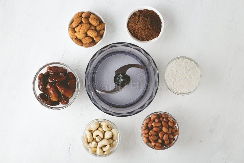Ingrediënten voor energiebeten: noten, data, cacaopoeder en kokosnotenvlokken met keukenmachine op witte lijst royalty-vrije stock foto