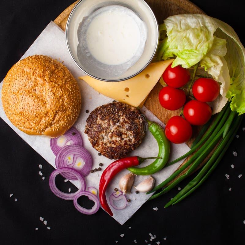 Ingrediënten voor hamburger op een donkere achtergrond Hoogste mening royalty-vrije stock foto