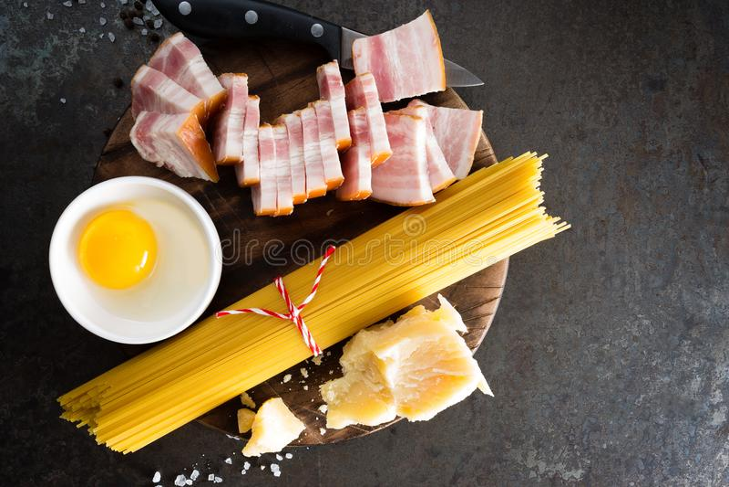 Ingrediënten voor het koken van Carbonara-deegwaren, spaghetti met pancetta, ei en harde parmezaanse kaaskaas Traditionele Italia stock foto