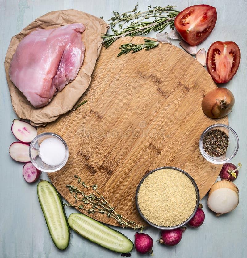 Ingrediënten voor het koken van de borst van Turkije met kouskous met groenten en kruiden op een scherpe raadsronde op houten pla stock afbeelding