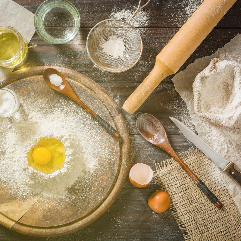Ingrediënten voor het koken van deeg of brood Gebroken ei bovenop een bos van witte roggebloem Donkere houten achtergrond royalty-vrije stock afbeeldingen