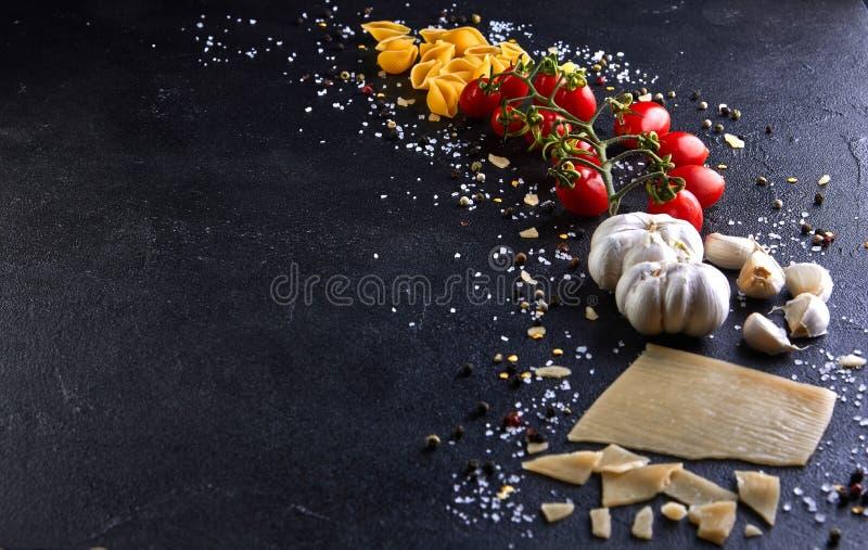 Ingrediënten voor het koken van deegwaren op een zwarte achtergrond stock fotografie