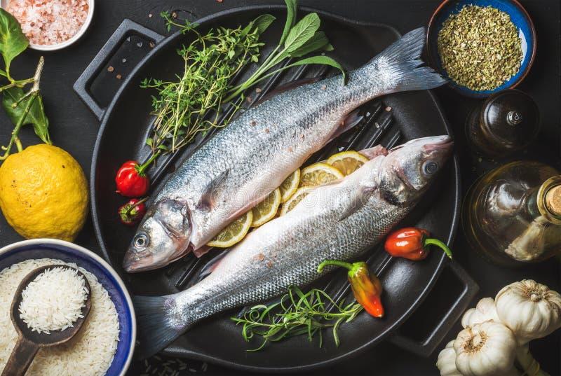Ingrediënten voor het koken van gezond vissendiner Ruwe ongekookte zeebaars met rijst, citroen, kruiden en kruiden bij het zwarte stock fotografie