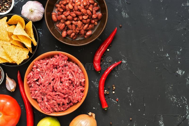 Ingrediënten voor het koken van Mexicaanse chili con carneschotels op een zwarte concrete achtergrond, hoogste mening De ruimte v royalty-vrije stock foto
