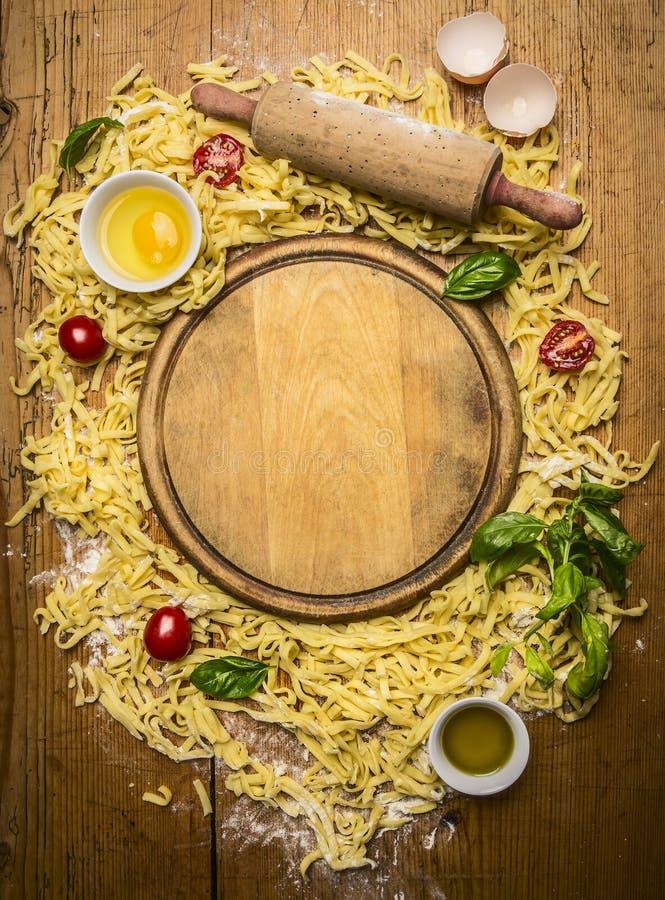 Ingrediënten voor het maken van deegwaren, Bloem, eieren, deegrol, kruid, olijfolie, rond scherpe raad op houten hoogste mening r royalty-vrije stock afbeelding