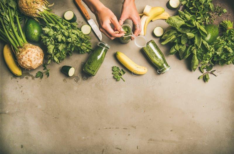 Ingrediënten voor het maken van groene smoothie en vrouwelijke handen houdend fles royalty-vrije stock afbeelding