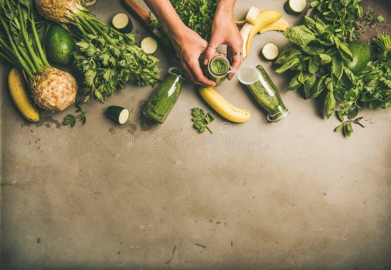 Ingrediënten voor het maken van groene smoothie en vrouwelijke handen met fles royalty-vrije stock afbeelding