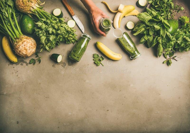 Ingrediënten voor het maken van groene smoothie en vrouwelijke handen met fles royalty-vrije stock foto's