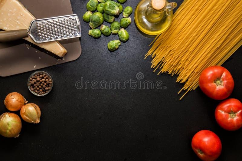 Ingrediënten voor Italiaanse Deegwaren Spaghetti, tomaten, olie, ui, parmezan op zwarte houten backg stock afbeelding