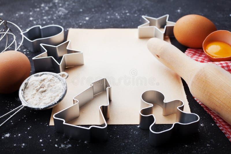 Ingrediënten voor Kerstmisbaksel Koekjessnijders, bloem, deegrol, eieren en document blad op keuken zwarte lijst royalty-vrije stock fotografie