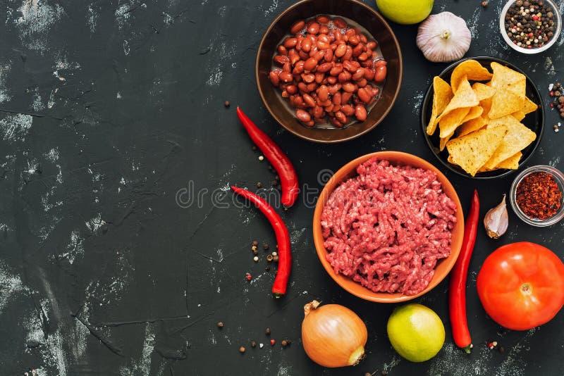 Ingrediënten voor Mexicaans schotelschili con carne Zwarte concrete achtergrond, hoogste mening, ruimte voor tekst stock afbeelding