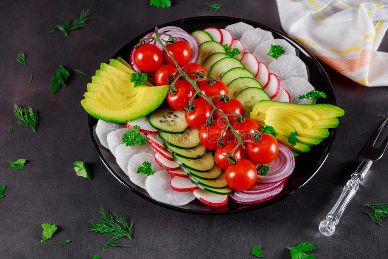 Ingrediënten voor plantaardige salade, verse tomaten, komkommer, avocado, sla, ui de grijze houten lijst, selectieve nadruk stock afbeeldingen