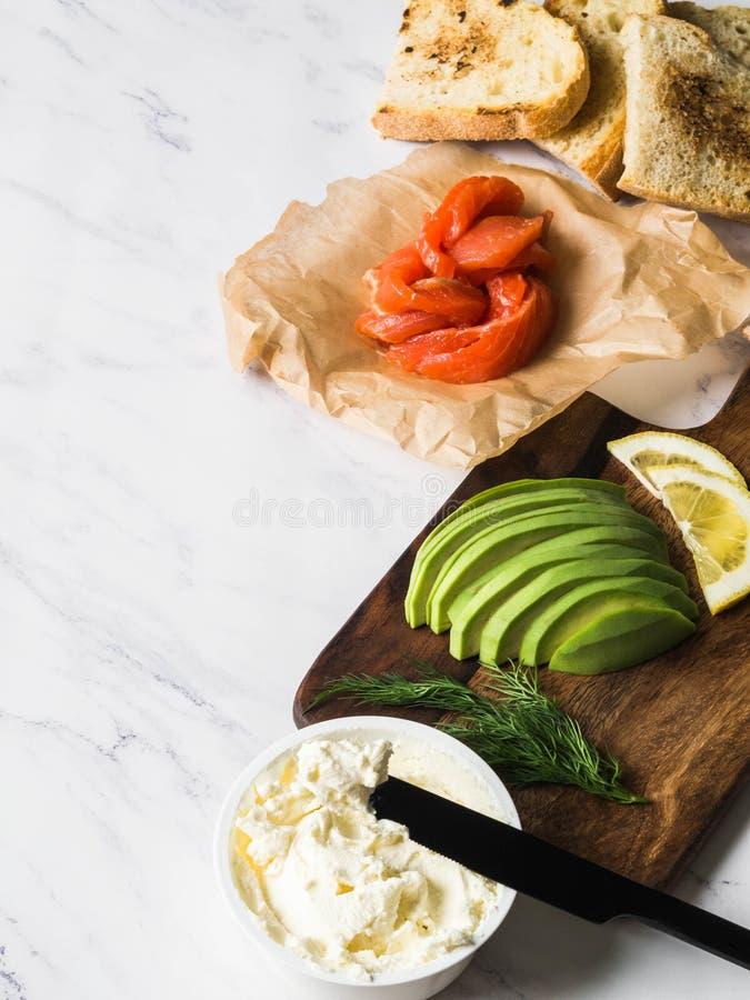 Ingrediënten voor voorbereidingssandwiches met roomkaas, zalm, avocado op geroosterde toosts op witte marmeren achtergrond De rui stock afbeelding