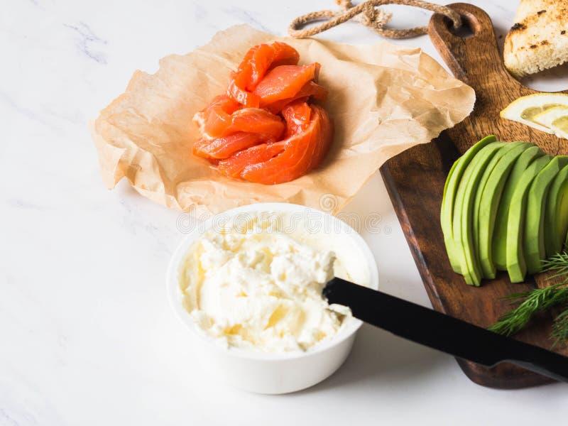 Ingrediënten voor voorbereidingssandwiches met roomkaas, zalm, avocado op geroosterde toosts op witte marmeren achtergrond De rui stock foto's