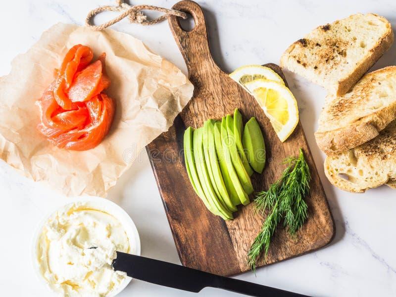 Ingrediënten voor voorbereidingssandwiches met roomkaas, zalm, avocado op geroosterde toosts op witte marmeren achtergrond Hoogst stock afbeeldingen