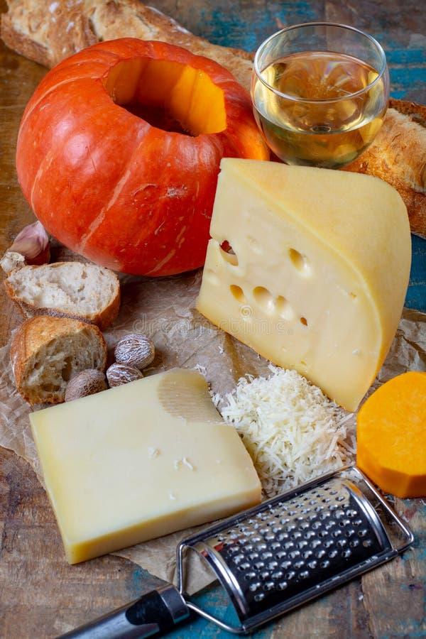 Ingrediens dla tradycyjnego sezonowego szwajcara naczynia, dyniowego fondue z serami, białego wina, gruyer i emmentaler, świeży c zdjęcia royalty free