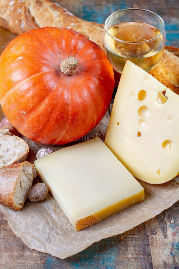 Ingrediens voor traditionele seizoengebonden Zwitserse schotel, pompoenfondue met gruyer en emmentalerkazen, witte wijn, verse ro stock foto