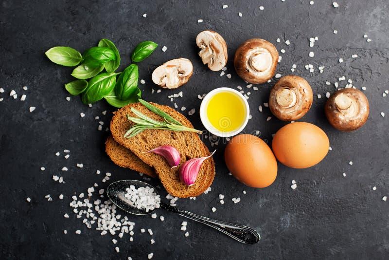 Ingredienser av sund n?ring Frukostf?rberedelse Ägg bröd, tomater, basilika, korvar, saltar, champinjoner royaltyfria foton