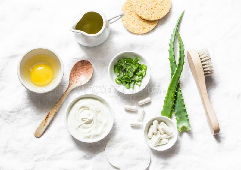 Ingredienser för aloeframsidamaskering - aloe, yoghurt, ägg, olivolja och skönhettillbehör på ljus bakgrund, bästa sikt Hem- rece royaltyfri bild