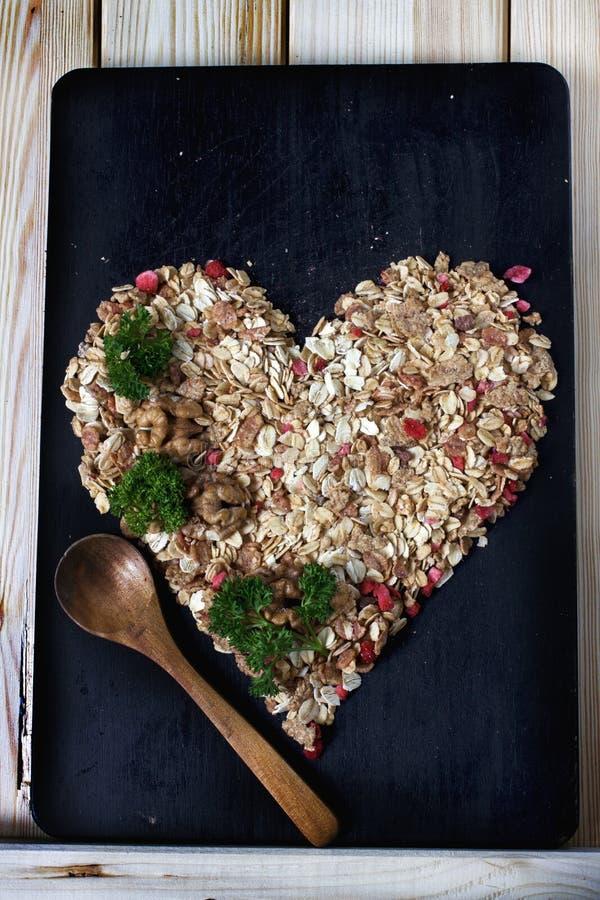 Ingredienser för att laga mat den sunda frukosten i en form av hjärta Muttrar havreflingor, torkade frukter, honung, granola royaltyfri foto