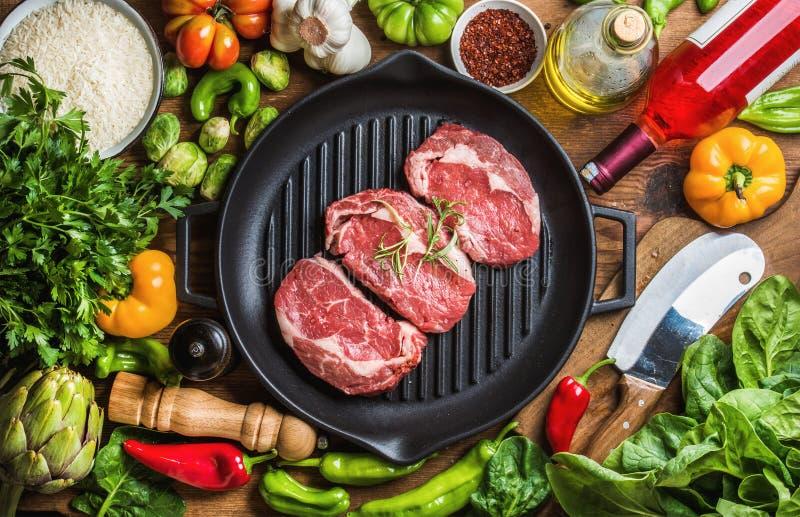 Ingredienser för att laga mat den sunda köttmatställen Rå okokta nötköttbiffar med grönsaker, ris, örter, kryddor och vin arkivbild