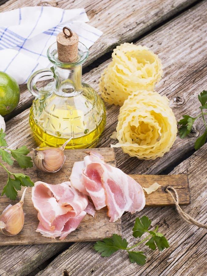 Ingredienser för att laga mat fusillipasta med bacongrönsaker fotografering för bildbyråer